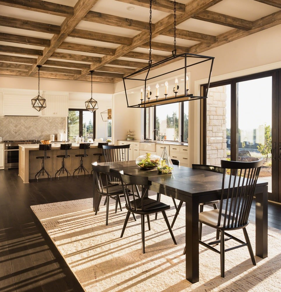 This is charming and homey dining area right by the kitchen under the same beige ceiling with exposed wooden beams. This hangs a decorative chandelier over the dark wooden dining table that matches with the wooden chairs and the hardwood flooring.