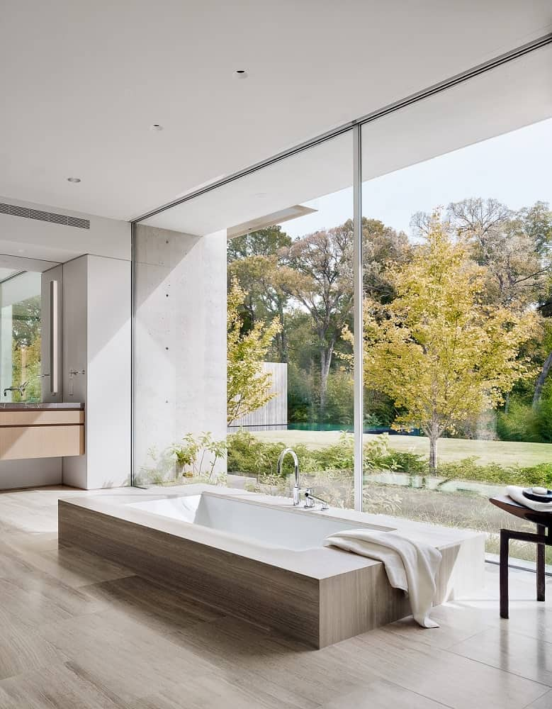 This is a close look at the bathroom's bathtub on the floor by the glass wall that has view of the surrounding landscape.