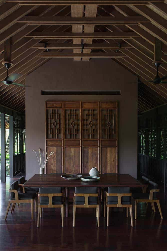 This is the dining room of the house that has a rectangular wooden dining table surrounded by cushioned chairs and topped with a wooden arched beamed ceiling and adorned with wooden panels on the far wall that has intricate carvings.