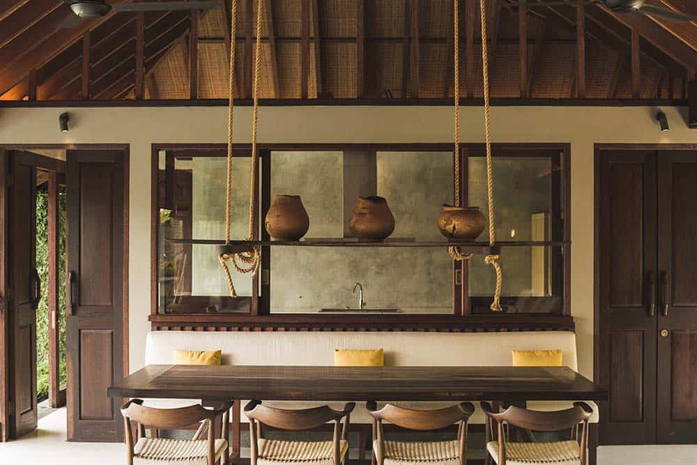 This is the dining area with a large wooden dining table surrounded by wooden chairs and topped iwth a tall wooden cathedral ceiling that hangs a wooden plank bearing earthen jars for display.
