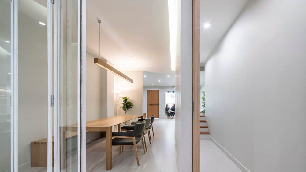 This is the dining room of the house with a simple bright white room that makes the wooden rectangular dining table stand out along with its dark cushioned chairs and modern lighting.