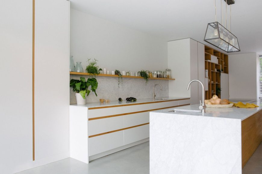 Carrara marble, oak, and off-white doors combine effortlessly to create this beautifully clean and simple kitchen in a huge 17m x 8m room.