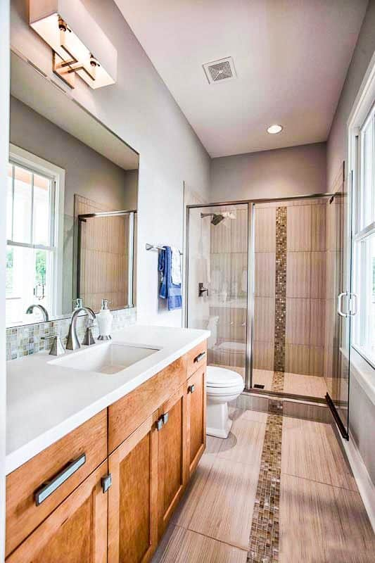 This bathroom has a wooden vanity topped with a large wall-mounted mirror that matches the glass enclosed shower area at the far end.