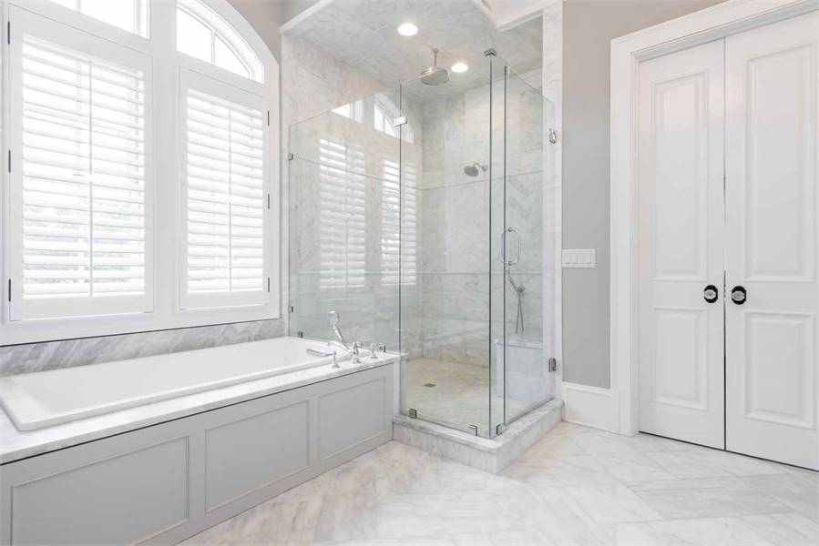 Across from the two-sink vanity is the glass-enclosed shower area beside the bathtub that is brightened by the white arched shuttered window above.