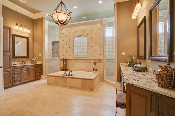This luxurious bathroom has has a consistent beige tone to its spacious floor and walls that are lit by the warmth of the dome pendant light. You can see here that the bathtub is inlaid with the same beige tiles as the floor and behind it is the wall of the walk-in shower area on the far end.