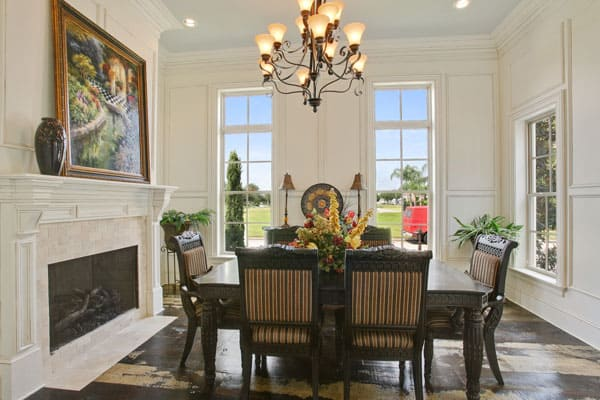 This is the formal dining room of the house with a majestic decorative chandelier hanging over the dark wood dining table that is warmed by the romantic fireplace topped with a large painting.