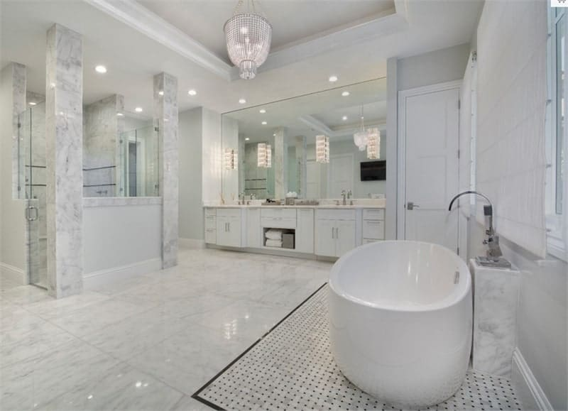 This primary bathroom with a freestanding tub, walk-in shower, and dual sink vanity paired with a large frameless mirror. These are all topped with a brilliant tray ceiling.