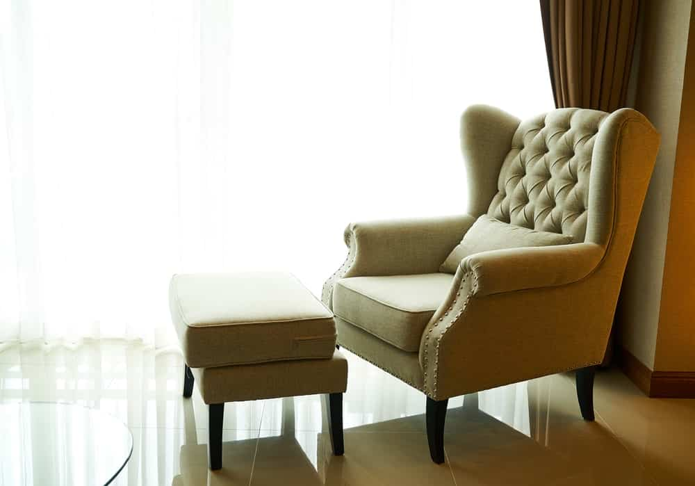 Upholstered chair with an ottoman by the window.