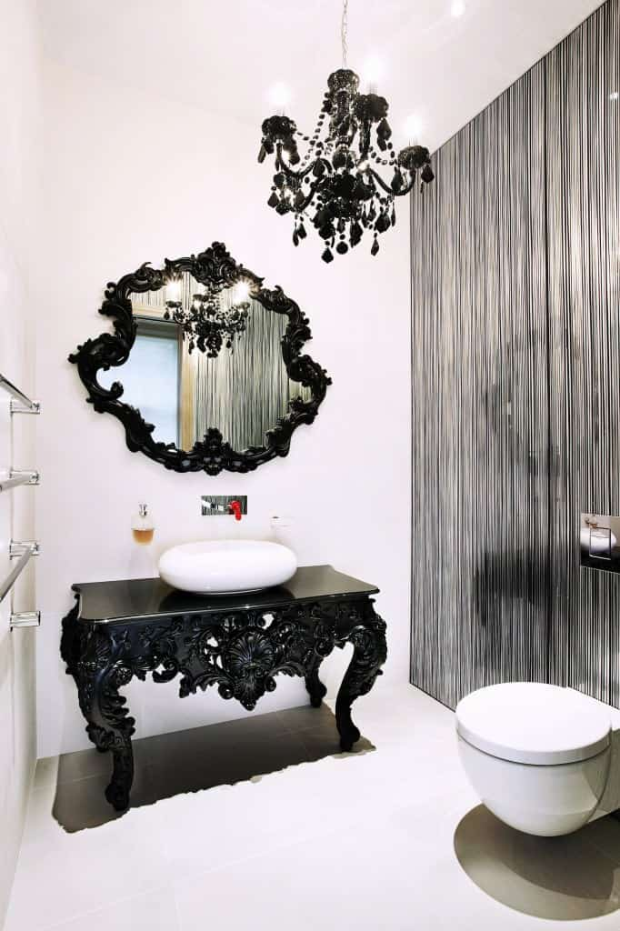 This beautiful Victorian-style bathroom has a unique black wooden table filled with elegant carvings. This perfectly matches with the vanity mirror and the chandelier for a unique aesthetic that contrasts the white flooring and walls.