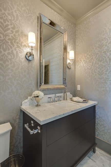 The elegant rectangular vanity mirror of this Victorian-style bathroom has a frame of stainless steel that goes well with the two modern wall-mounted lamps flanking it. This is an elegant foreground for the subtle patterns of the wallpaper and the contrasting black wooden vanity.