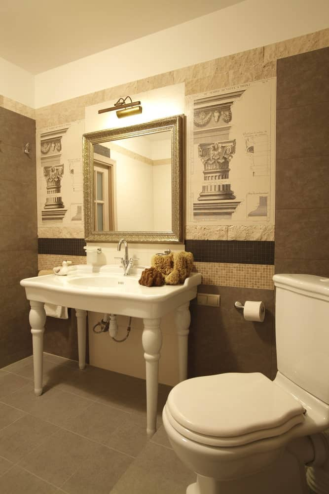 This simple bathroom has a porcelain toilet that matches with the sink that has white pencil legs contrasting the gray flooring tiles and the walls. The wall behind the gold-framed vanity mirror is different from the rest with its depictions of Greek columns on textured beige walls.