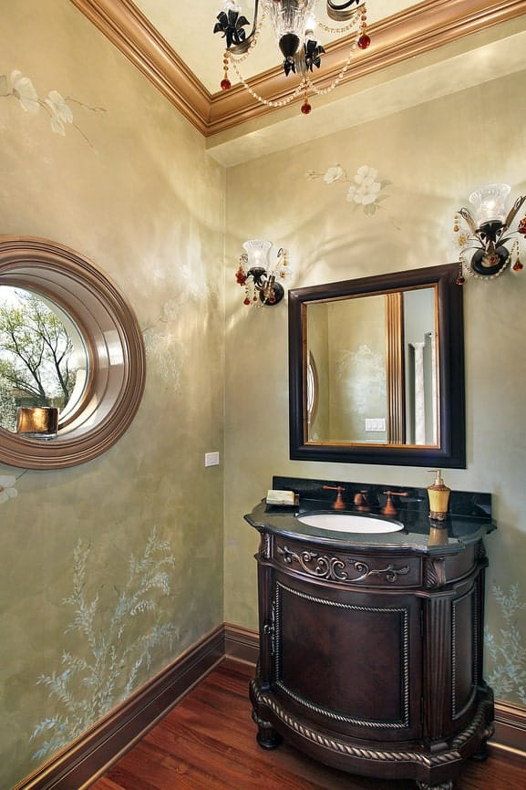 This chic Victorian-style bathroom has an avocado green wallpaper accented with flower portraits. This provides a nice background for the round window and square vanity mirror with dark wooden frames matching the carved vanity.