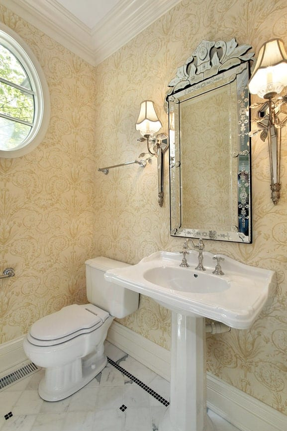 This brilliant bathroom has intricate patterns on its beige wallpaper that alsmost glows golden with the yellow lights of the wall-mounted lamps flanking the peculiar vanity mirror above the white pedestal sink that pairs well with the toilet.