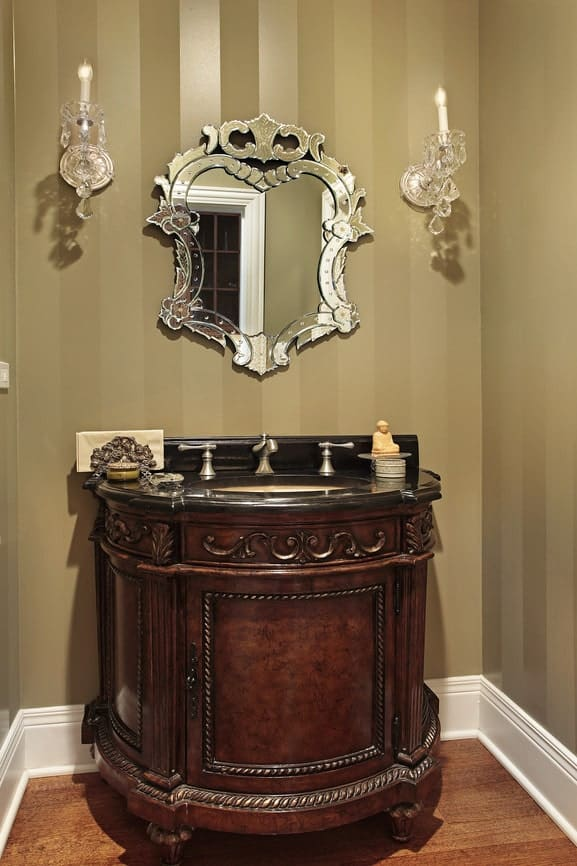 The walls of this Victorian-style bathroom has a gray striped palette to it that is a perfect background for the elegant wooden vanity framed with carvings topped with a black countertop and backsplash contrasted by the silver faucet that matches the intricate vanity mirror flanked by crystal wall lamps.