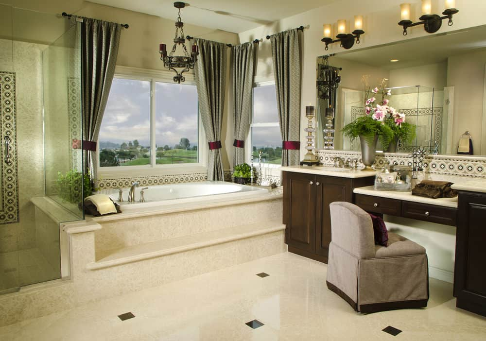 The elegant gray curtains flanking the windows of the bathtub inlaid with the same beige marble of the flooring match with the wrought iron chandelier. This is paired well with the wall-mounted lamps above the vanity mirror.