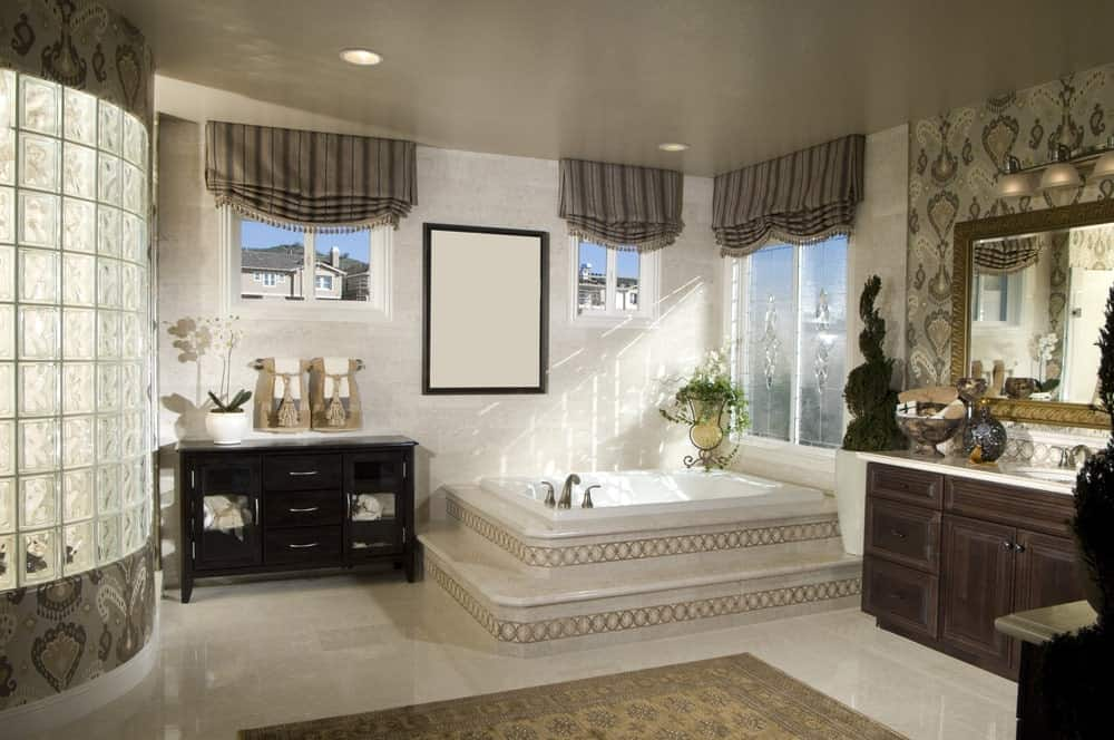 The wall behind the gold-framed vanity mirror has intricate gray patterns matching with those framing the curved wall of the shower area that has frosted glass panels. The gray ceiling is contrasted by the beige marble flooring that makes the dark wooden vanity beside the corner tub stand out.