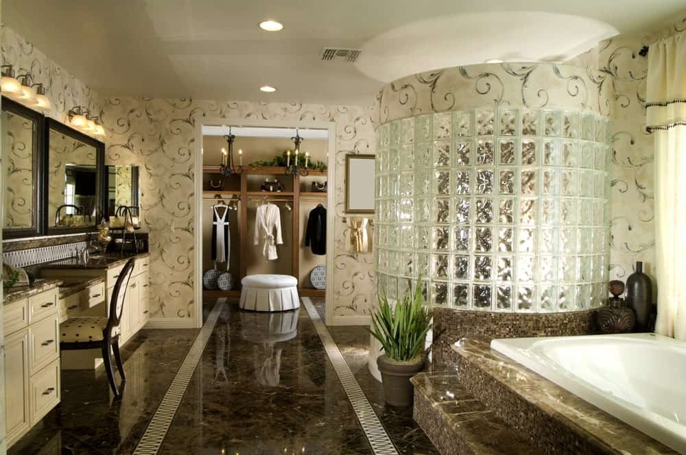 The sleek and dark marble flooring is a nice contrast to the beige wooden two-sink vanity that blends with the beige wallpaper that has an intricate vine design. This goes well with the frosted glass of the shower area and the bathtub inlaid with the same marble as the flooring.