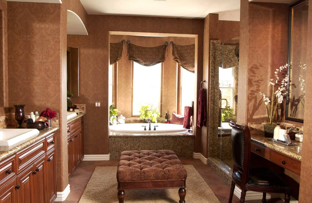 The brown wallpaper of the walls have intricate elegant patterns matching those of the curtains of the bathtub windows as well as the tufted wooden stool in the middle of the terracotta flooring topped with an area rug.