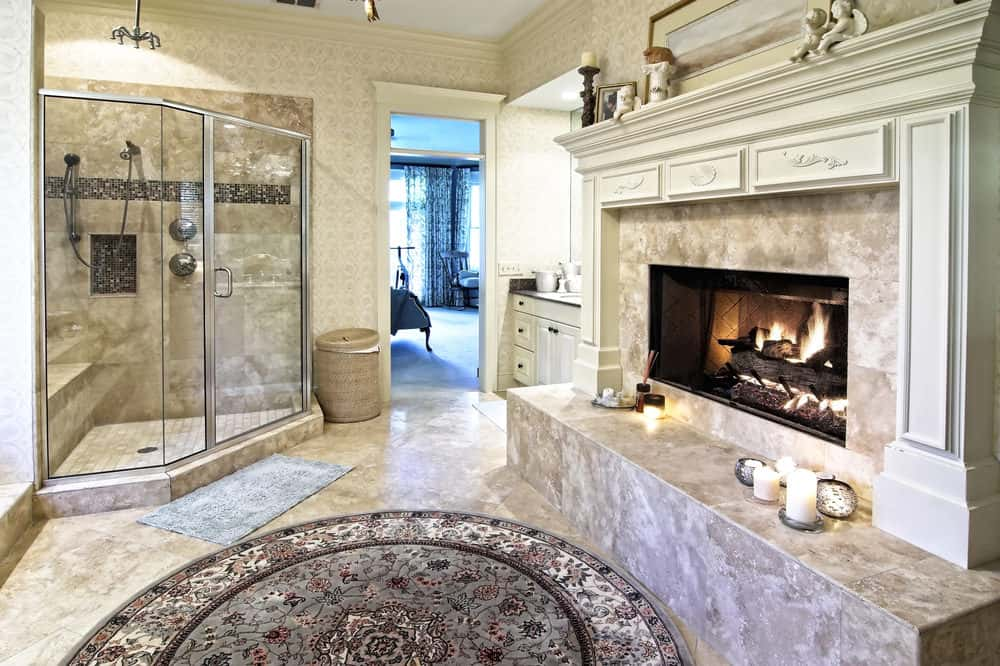 This charming luxurious bathroom is dominated by a large fireplace inlaid with the same gray marble as the flooring and the walls of the glass-enclosed shower area. The white mantle of the fireplace has an elegant finish augmented by the beige patterned wallpaper and the round patterned area rug.