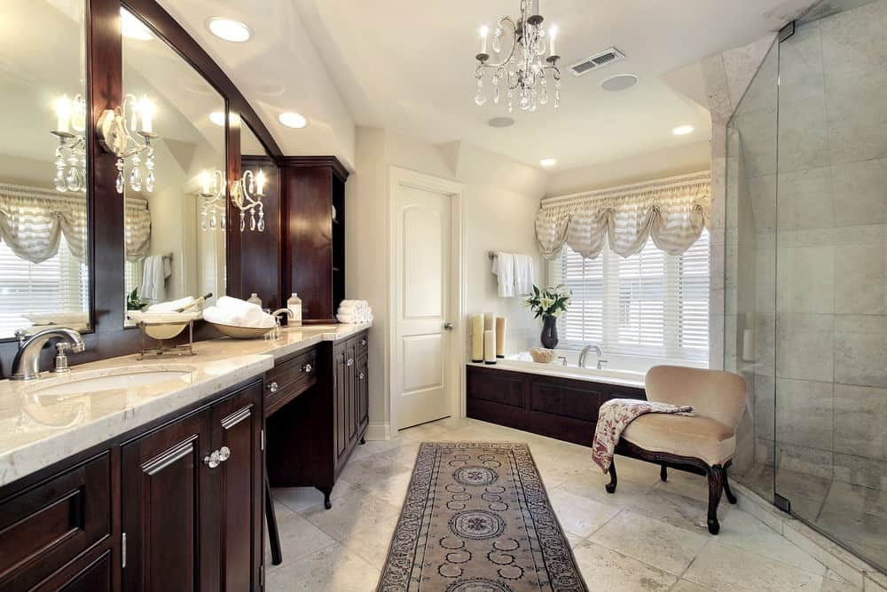 The crystal wall lamps flanking the mirrors of the wooden vanity match well with the brilliant crystal chandelier hanging over the gray patterned area rug over the off-white flooring contrasted by the dark wooden housing of the bathtub in an alcove.