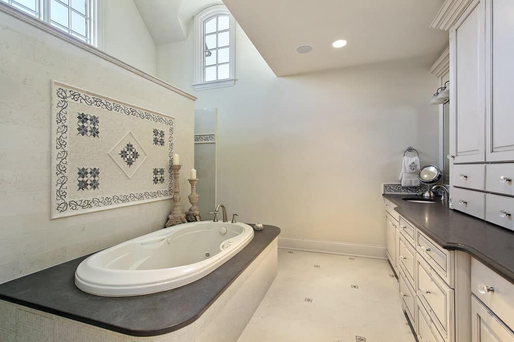 The dark countertop of the two-sink vanity matches with the elliptical bathtub housed with a dark countertop with a beige side blending with the flooring. This bathtub is separated from the shower high ceiling shower area by a beige wall adorned with stone wall-art.