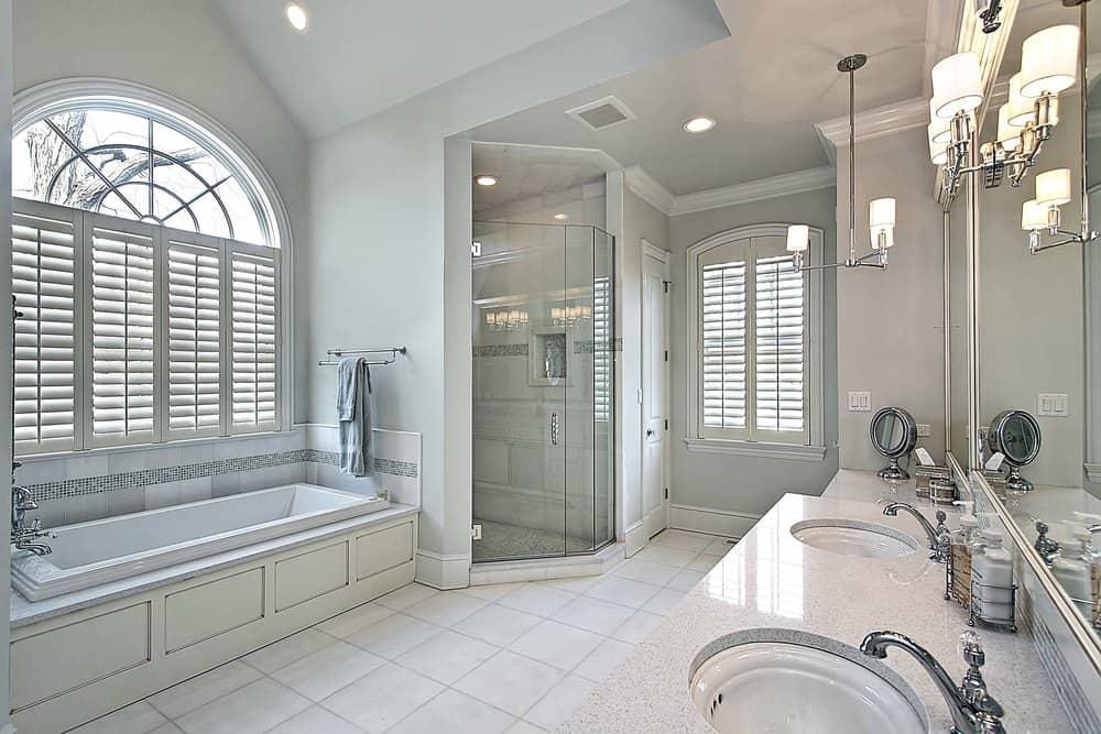 The white rectangular bathtub is by a large arched window with white shutters matching the wooden housing of the bathtub across from the long vanity area topped with modern lantern-like lamps that brightens the light gray walls and ceiling.
