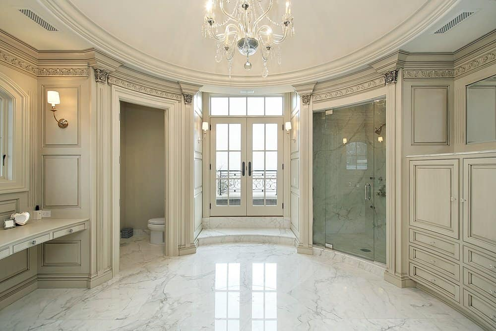 This brilliant Victorian-style bathroom has a round white tray ceiling with a brilliant crystal chandelier in the middle hanging over the white marble flooring that complements the light gray wooden walls and built-in structures that has elegant carvings and designs.
