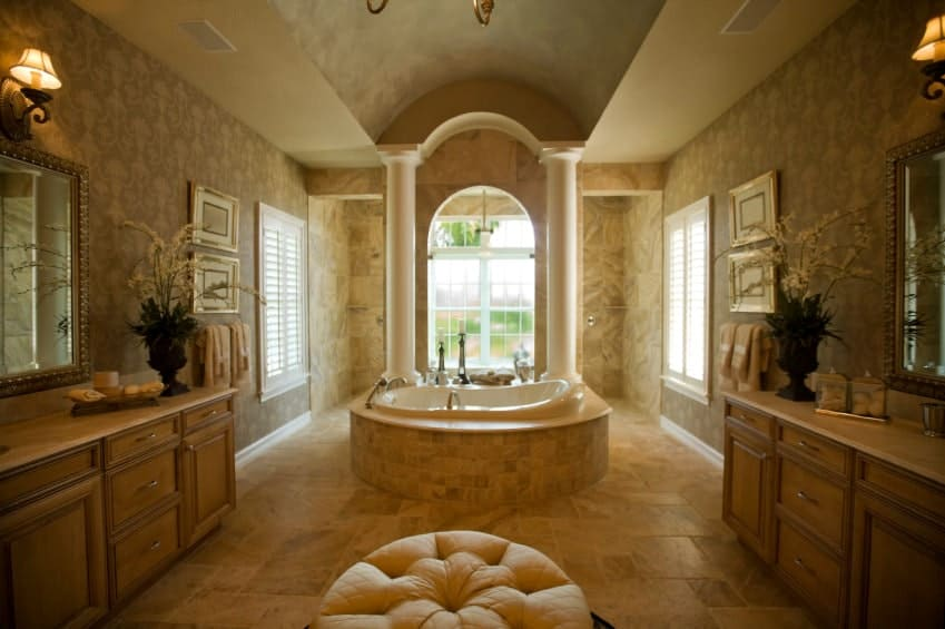 The elongated cove beige ceiling has a pair of white pillars flanking the arched window of the bathtub that is housed with the same beige marble as the flooring that perfectly pairs with the elegant patterns of the wallpaper. This is complemented by the wrought iron wall-lamps of the two wooden vanities.