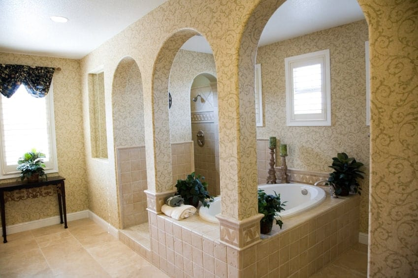 The bathtub adorned with potted plants is complemented by three arches filled with beige wallpaper that has intricate vine patterns the same as the walls contrasted by the white window frames and the white ceiling with recessed lights.