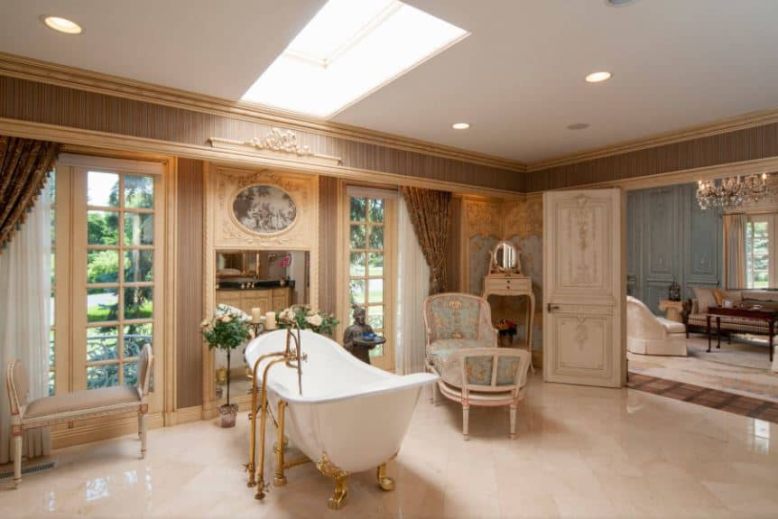 This is an elegant and chic Victorian-style bathroom that boasts a freestanding bathtub in the middle of the white flooring contrasted by the golden legs of the bathtub that matches its golden fixtures. The rest of the bathroom looks more like a living room with its cushioned chairs and elegant floral elements.