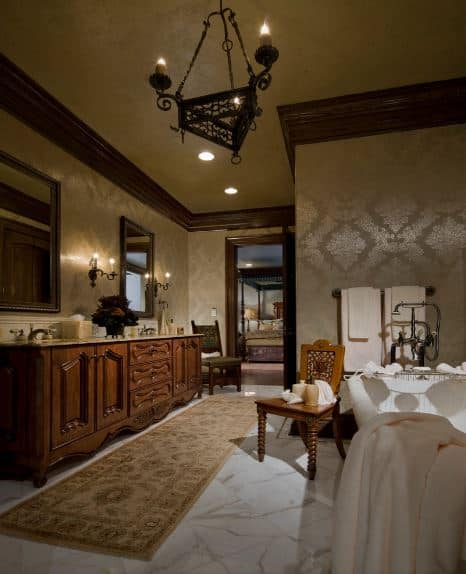 The white marble flooring of this luxurious bathroom is topped with a long beige patterned area rug by the wooden vanity large enough for two sink areas with its own mirrors accented by wrought iron wall lamps that match the chandelier over the bathtub.