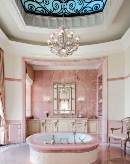 This charming pink bathroom is a perfect fusion between chic and Victorian-style elements like the pink countertop of the round bathtub that has elegant fixtures topped with an intricate chandelier matching the wall lamps of the pink-walled vanity area.