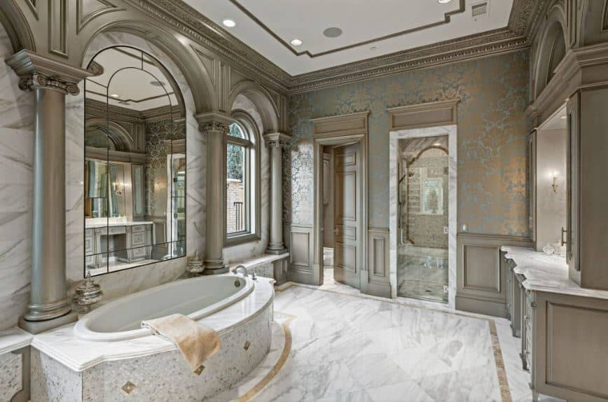 The white tray ceiling is paired with white marble flooring that contrasts the gray walls with subtle patterns to its wallpaper. This goes well with the gray columns and arches with elegant carvings and design.