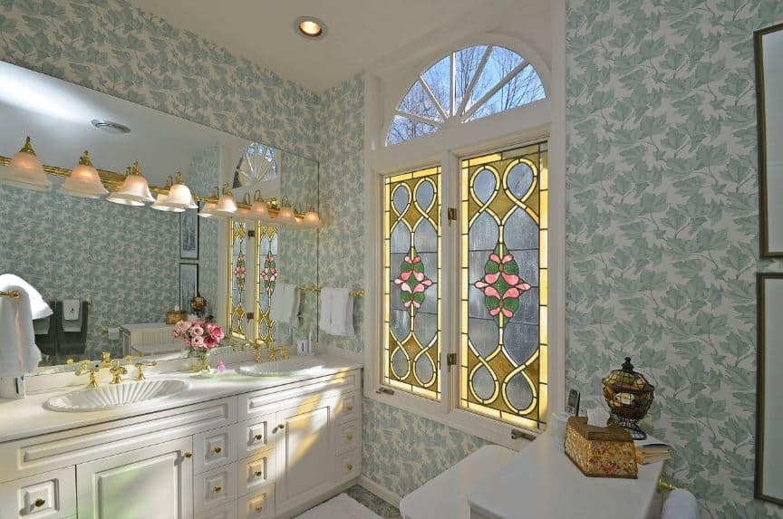The highlight of this Victorian-style bathroom is the awe-inspiring stained glass windows framed with white wood that matches the adjacent white vanity with white countertops and two sinks with shell design topped with golden faucets that match the golden wall lamps mounted on the large vanity mirror.