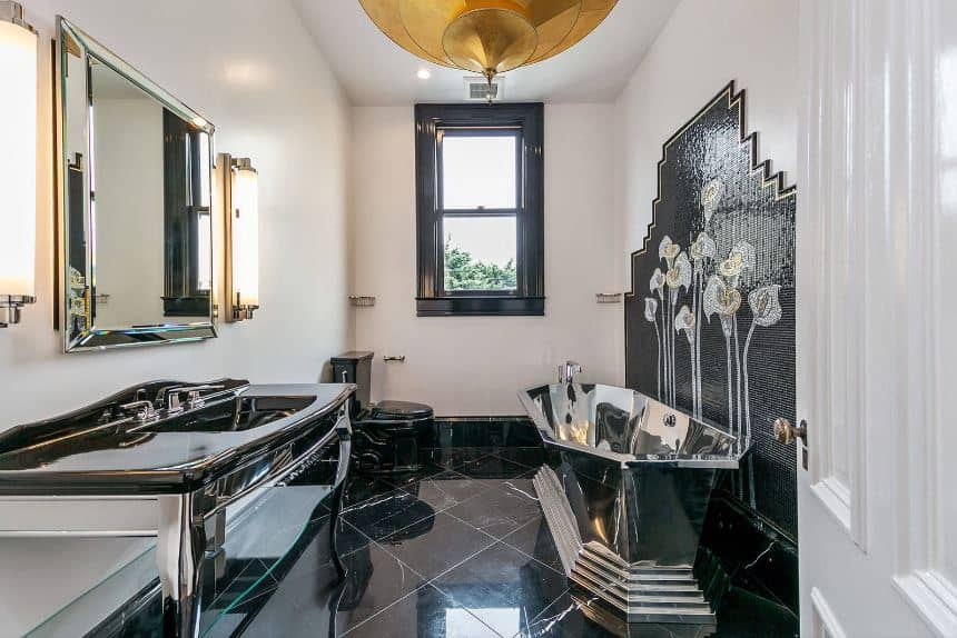 The unique stainless steel freestanding bathtub is the highlight of this Victorian-style bathroom with sleek black marble floors topped with a large golden dome lighting hanging from the white ceiling.