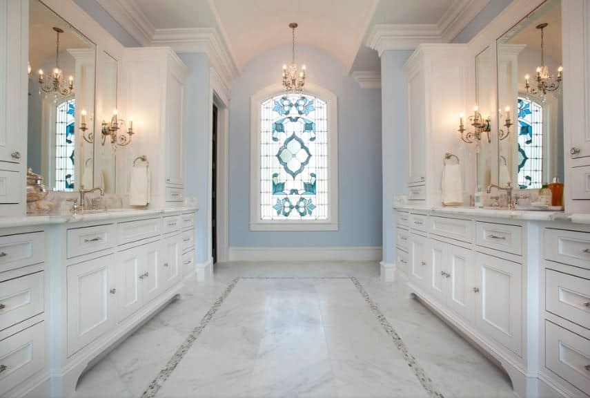 This bright Victorian-style bathroom has white wooden vanities that blend with the white marble flooring and the white cove ceiling. This is complemented by the light blue walls matching the stained glass of the large window on the far wall.