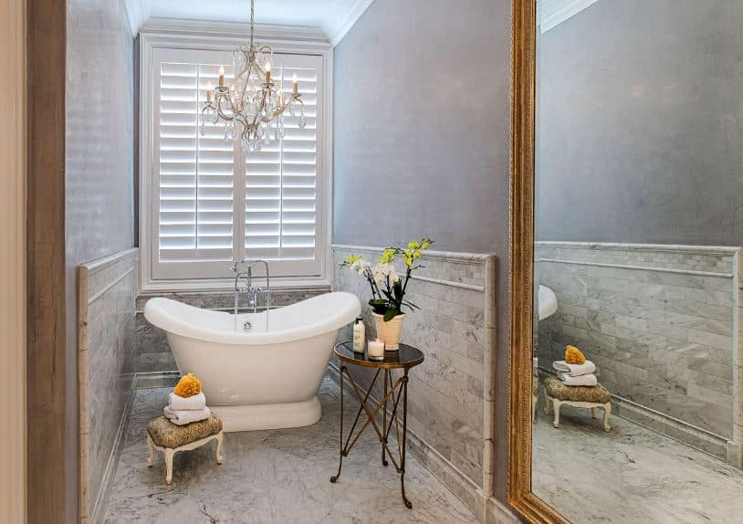 An elegant crystal chandelier hangs over the small freestanding bathtub that is situated in a narrow alcove that has light gray upper walls brightened by the natural lights coming in from the white shuttered window.