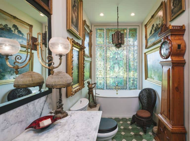 This charming and homey bathroom is almost filled to the brim with decors for a unique museum-like aesthetic paired with a green patterned flooring that makes the freestanding bathtub stand out adorned with a majestic stained glass window.