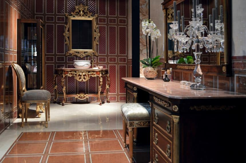 The patterned and elegantly-designed red walls are adorned with an elegant and intricate frame of the vanity mirror above the table vanity with the same designs. This is paired with another wooden table over a section of the flooring that has earthy tones.