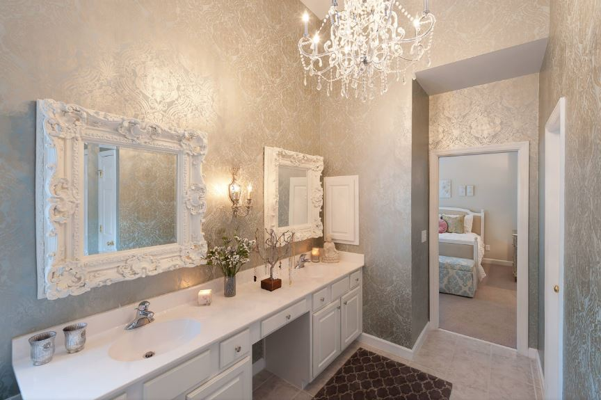 The brilliant silver wallpaper has subtle elegant patterns on it that complements the white intricate chandelier that brightens the white frames of the vanity mirror with carvings over the white wooden two-sink vanity.