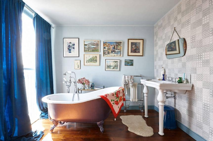 The copper-toned freestanding bathtub that goes well with the hardwood flooring is facing a large bright window flanked with blue drapes complemented by the light blue ceiling and walls that are filled with framed artworks and paintings.