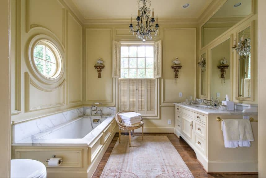 The yellow walls that blend with the yellow wooden structures housing the bathtub and sink have an elegant finish adorned with a circular window and artworks that go well with the crystal chandelier hanging from the white ceiling.