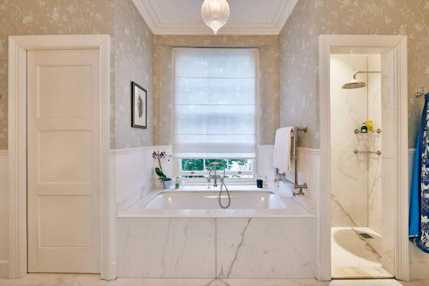 The small white bathtub of this Victorian-style bathroom is in the middle of an alcove with a single white window flanked by walls dominated by a wallpaper with an earthy tone background to the subtle patterns.