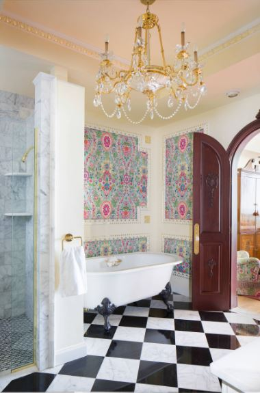 This simple bathroom is elevated by the eclectic combination of different patterns that somehow works from the black and white checkered flooring to the colorful floral walls topped with a majestic gold and crystal chandelier.