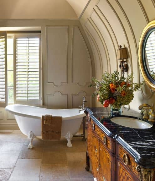 The light gray walls of this spacious bathroom curves to a cove ceiling with a beige hue complementing the light gray finish of the walls contrasted by the stark white freestanding bathtub by the shuttered window.