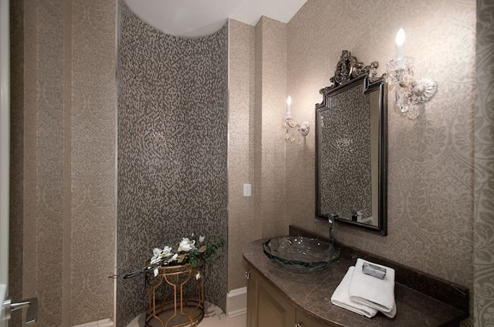 A beautiful glass bowl basin sink stands out against the dark countertop of the vanity matching the curved wall alcove on the side flanked by gray wallpaper with intricate patterns illuminated by white crystal wall lamps on either side of the vanity mirror.