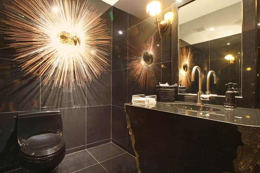 The black porcelain toilet blends in with the black flooring tiles and wall tiles that are accented by the sun-like artwork mounted over the toilet adjacent to the yellow light of the brass wall lamp beside the mirror of the glass-top vanity.