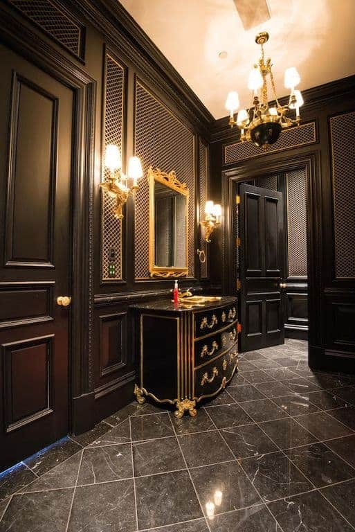 The black marble flooring matches with the black wooden elegant finish of the walls. This is accented by the gold elements seen on the black curved vanity, vanity mirror and wall-mounted lamps that match the amazing chandelier.