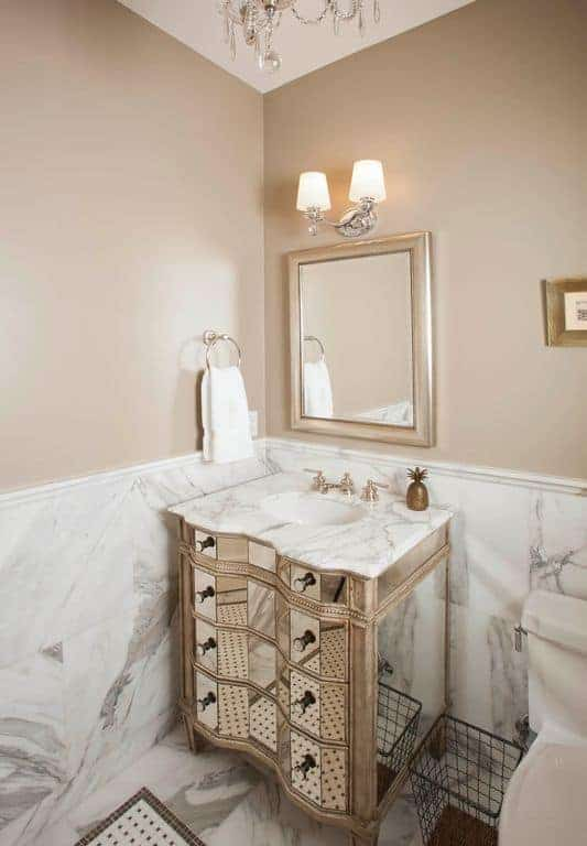 The small curved vanity has a mirror facade on its drawers reflecting the white marble flooring and walls blending with its countertop that complements the light gray walls adorned with small framed artworks and a vanity mirror.
