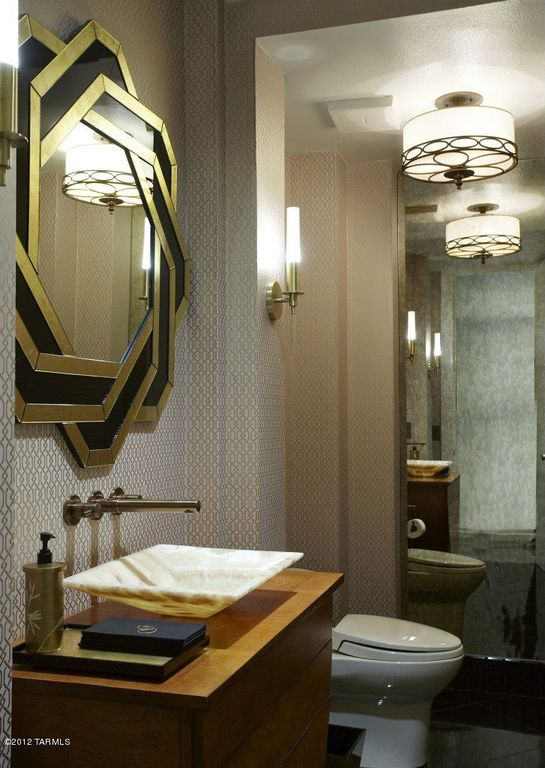 The gold and black vanity mirror has a rose-like design to it that is complemented by the semi-flush lighting mounted on the white textured ceiling perfectly contrasted by the gray patterned wallpaper that makes the wooden vanity stand out.